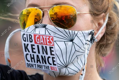 "The Reichstag building, home of the German federal parliament, is mirrored in the glasses of a woman wearing a face mask with the slogan ""Don't Give (Bill) Gates A Chance"" during a demonstration against restrictions and measures to prevent the spread of the new coronavirus in Berlin, Germany"