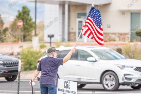 Robert Taylor waves a flag and encourages traffic in support of C&C Coffee & Kitchen's reopening at its Colorado Springs location on May 16. The business made national news as its license was revoked after opening the dining area of their Castle Rock location on Mother's Day, with allegations of improper social distancing. While the Castle Rock location, in Douglas County, remains closed, the Colorado Springs location falls within El Paso County health guidlines, which are in the process of being modified after a vote earlier this week to allow for limited eat-in dining. Saturday was the first day the Colorado Springs location reopened for business since the closure earlier this week.