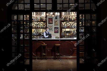 """Barman Nicholas Pinna wears a protective face mask as he stands behind the cocktail bar of the art-deco style Locarno Hotel, in Rome, Monday, May 11, 2020. Pinna is looking forward to a return to normality, he says he has """"lots of hope to restart soon, to see again all our clients which we were used to see here, and to return to working with maximum serenity"""" as the hotel prepares to welcome back its clients, hopefully soon"""