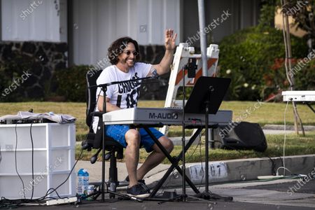 Musician Adam Chester reacts as he performs during his weekly neighborhood concert called 'Quaranchella' amid the coronavirus disease (COVID-19) pandemic in Sherman Oaks, North-West of Los Angeles, California, 16 May 2020. Adam Chester, who earned the title of the 'Surrogate Elton John' for singing and playing the rock star's parts at rehearsals, organizes these weekly concerts for his neighbors and to raise money for 'The Man/Kind Project'.