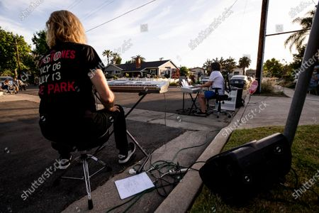 Musicians Kim Bullard (L) and Adam Chester perform during Chester's weekly neighborhood concert called 'Quaranchella' amid the coronavirus disease (COVID-19) pandemic in Sherman Oaks, North-West of Los Angeles, California, 16 May 2020. Adam Chester, who earned the title of the 'Surrogate Elton John' for singing and playing the rock star's parts at rehearsals, organizes these weekly concerts for his neighbors and to raise money for 'The Man/Kind Project'.
