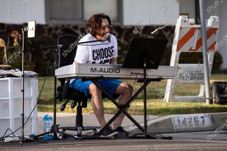 Musician Adam Chester performs during his weekly neighborhood concert called 'Quaranchella' amid the coronavirus disease (COVID-19) pandemic in Sherman Oaks, North-West of Los Angeles, California, 16 May 2020. Adam Chester, who earned the title of the 'Surrogate Elton John' for singing and playing the rock star's parts at rehearsals, organizes these weekly concerts for his neighbors and to raise money for 'The Man/Kind Project'.