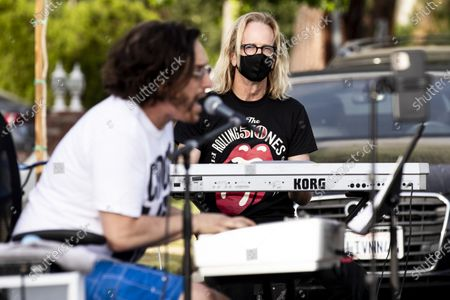 US musician Kim Bullard (R) and Adam Chester (L) perform during Chester's weekly neighborhood concert called 'Quaranchella' amid the coronavirus disease (COVID-19) pandemic in Sherman Oaks, North-West of Los Angeles, California, 16 May 2020. Adam Chester, who earned the title of the 'Surrogate Elton John' for singing and playing the rock star's parts at rehearsals, organizes these weekly concerts for his neighbors and to raise money for 'The Man/Kind Project'.