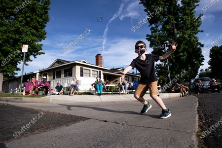 A kid dances as musician Adam Chester performs during his weekly neighborhood concert called 'Quaranchella' amid the coronavirus disease (COVID-19) pandemic in Sherman Oaks, North-West of Los Angeles, California, 16 May 2020. Adam Chester, who earned the title of the 'Surrogate Elton John' for singing and playing the rock star's parts at rehearsals, organizes these weekly concerts for his neighbors and to raise money for 'The Man/Kind Project'.