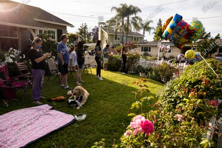 Neighbors listen to musician Adam Chester performing during his weekly neighborhood concert called 'Quaranchella' amid the coronavirus disease (COVID-19) pandemic in Sherman Oaks, North-West of Los Angeles, California, 16 May 2020. Adam Chester, who earned the title of the 'Surrogate Elton John' for singing and playing the rock star's parts at rehearsals, organizes these weekly concerts for his neighbors and to raise money for 'The Man/Kind Project'.