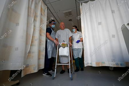 Stock Image of Occupational Therapists Jason Smith and Grace Rowan assist recovering coronavirus patient Peter Dunn in walking again after leaving intensive care at The Royal Blackburn Teaching Hospital in East Lancashire, following the outbreak of the coronavirus disease (COVID-19) in Blackburn, Britain, 14 May 2020. Several countries around the world have started to ease COVID-19 lockdown restrictions in an effort to restart their economies and help people in their daily routines after the outbreak of coronavirus pandemic.