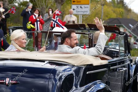 Norway's Crown Princess Mette-Marit (L) and Crown Prince Haakon sit in a convertible car as they attend the May 17th celebrations outside their home Skaugum in Asker, Norway, 17 May 2020.  The Constitution Day is celebrated in a new and different way this year because of the coronavirus.