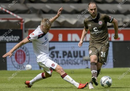 St. Pauli's Rico Benatelli (R) and Hanno Behrens of FC Nuremberg in action during the German Bundesliga second division soccer match between FC St. Pauli and 1. FC Nuremberg in Hamburg, Germany, 17 May 2020. The Bundesliga and Second Bundesliga is the first professional league to resume the season after the nationwide lockdown due to the ongoing Coronavirus (COVID-19) pandemic. All matches until the end of the season will be played behind closed doors.