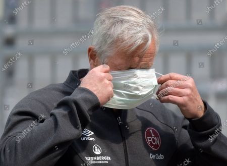 Coach of FC Nuremberg, Jens Keller, adjusts his protective face mask during the German Bundesliga second division soccer match between FC St. Pauli and 1. FC Nuremberg in Hamburg, Germany, 17 May 2020. The Bundesliga and Second Bundesliga is the first professional league to resume the season after the nationwide lockdown due to the ongoing Coronavirus (COVID-19) pandemic. All matches until the end of the season will be played behind closed doors.