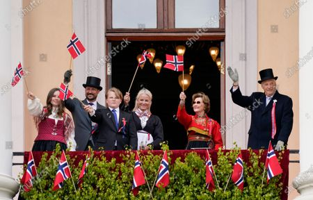 Stock Image of Norway's (R-L) King Harald, Queen Sonja, Crown Princess Mette-Marit, Prince Sverre Magnus, Crown Prince Haakon and Princess Ingrid Alexandra wave from a balcony of the palace as they attend the May 17th celebrations outside their home Skaugum in Oslo, Norway, 17 May 2020. This year, celebrations of the Scandinavian kingdom's national holiday are starkly different to the habitual revelry due to the ongoing pandemic of the COVID-19 disease caused by the SARS-CoV-2 coronavirus. Patriotic decorations have come to the forefront, with the main gates of Oslo's Royal Palace adorned with hydrangea, birch and ribbons sporting the national colors (red, white and indigo blue). The holiday commemorates the 1814 signing of the Norwegian constitution that declared the realm to be an independent kingdom after centuries of dynastic union with Denmark.