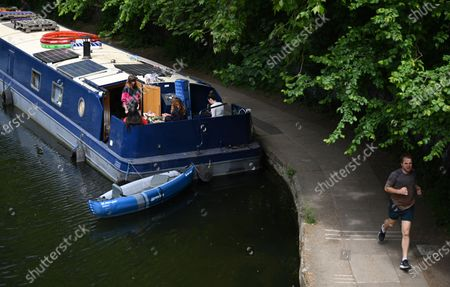 People relax on a canal boat on a a canal near Victoria park in London, Britain, 17 May 2020. Boris Johnson continues his plan to reopen Britain after weeks of measures to stem the spread of the SARS-CoV-2 coronavirus which causes the Covid-19 disease. People who can't work from home are now actively encouraged to return to workplaces, but use of public transport is being discouraged. More outdoor activity is allowed, as is meeting one person from another household under limited circumstances.