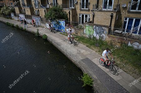 People cycle along a canal near Victoria park in London, Britain, 17 May 2020. Boris Johnson continues his plan to reopen Britain after weeks of measures to stem the spread of the SARS-CoV-2 coronavirus which causes the Covid-19 disease. People who can't work from home are now actively encouraged to return to workplaces, but use of public transport is being discouraged. More outdoor activity is allowed, as is meeting one person from another household under limited circumstances.