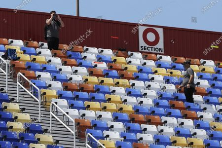 Officials monitor empty grandstands at Darlington Raceway before the start of the Real Heroes 400 NASCAR Cup Series auto race, in Darlington, S.C