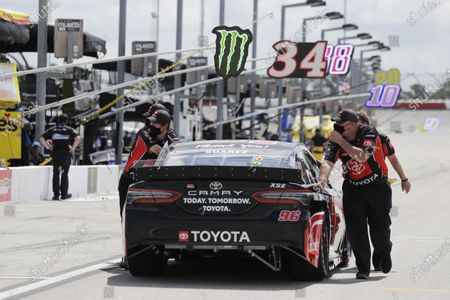 The car of Daniel Suarez is pushed along pit row in Darlington Raceway before the Real Heroes 400 NASCAR Cup Series auto race, in Darlington, S.C
