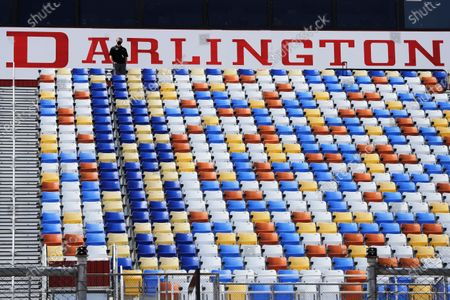 Man stands in an otherwise empty grandstand at Darlington Raceway before the Real Heroes 400 NASCAR Cup Series auto race, in Darlington, S.C