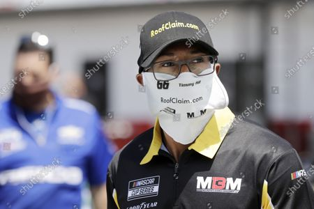 Crew member for driver Timmy Hill wears a mask as he works in the infield before the start of the Real Heroes 400 NASCAR Cup Series auto race, in Darlington, S.C