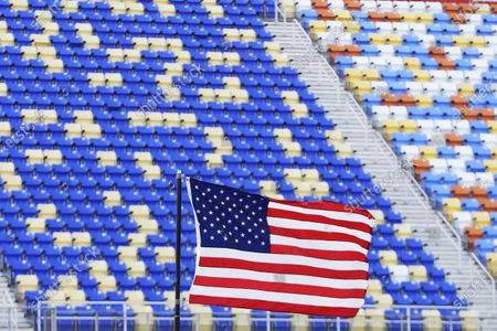 Flag flies in front of empty grandstands at Darlington Raceway before the Real Heroes 400 NASCAR Cup Series auto race, in Darlington, S.C. No fans are allowed in the facility because of the coronavirus pandemic