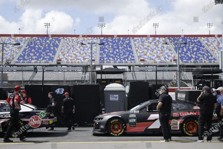 Cars sit with empty grandstands behind at Darlington Raceway, in Darlington, S.C. NASCAR, which has been idle for 10 weeks because of the coronavirus pandemic, makes its return with the Real Heroes 400 Nascar Cup Series auto race Sunday
