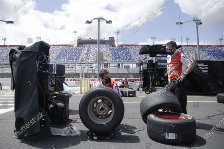 Crew members for driver Matt DiBenedetto prepare tires before the Real Heroes 400 NASCAR Cup Series auto race, in Darlington, S.C