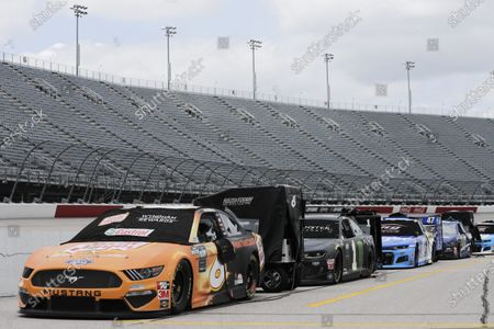 Cars are lined up with empty grandstands behind them before the NASCAR Cup Series auto race, in Darlington, S.C