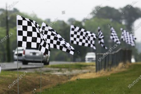 Checkered flags line a street outside Darlington Raceway, in Darlington, S.C. NASCAR, which has been idle since March 8 because of the coronavirus pandemic, makes its return with the Real Heroes 400 Nascar Cup Series auto race Sunday
