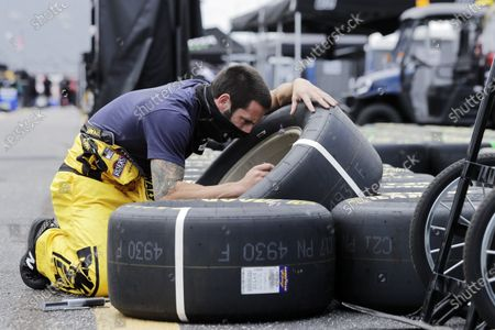 Tires are checked by a crew member for driver Erik Jones before the start of the NASCAR Cup Series auto race, in Darlington, S.C