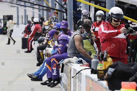 Crew members and officials wait in the pit area before the start of the NASCAR Cup Series auto race, in Darlington, S.C