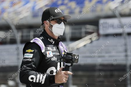 Driver Jimmie Johnson carries a camera as he walks to his car for the start of the NASCAR Cup Series auto race, in Darlington, S.C