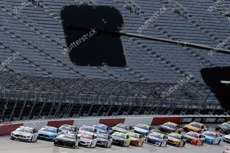 Cars approach the starting line in front of empty stands to start the NASCAR Cup Series auto race, in Darlington, S.C