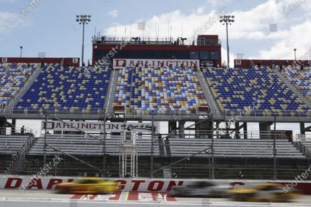 Cars pass by empty seats during the NASCAR Cup Series auto race, in Darlington, S.C