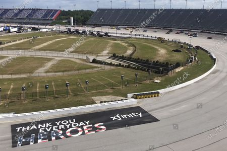 Cars go through a turn past a sign thanking people working during the coronavirus pandemic at Darlington Raceway, in Darlington, S.C. NASCAR, which has been idle for 10 weeks because of the pandemic, made its return with the Real Heroes 400 Nascar Cup Series auto race