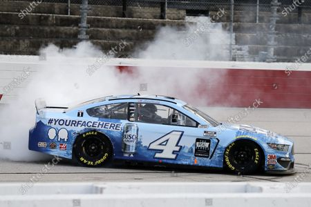 Kevin Harvick does a burnout after winning the NASCAR Cup Series auto race, in Darlington, S.C