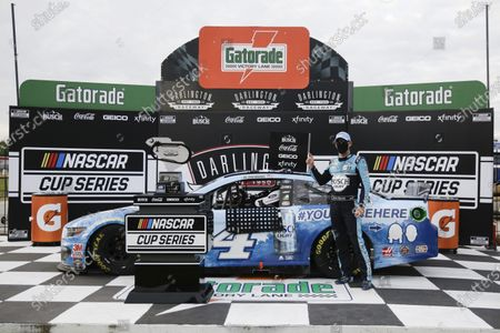 Kevin Harvick celebrates in victory lane after winning the NASCAR Cup Series auto race, in Darlington, S.C