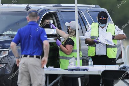 Driver Erik Jones gets his temperature taken as he arrives at Darlington Raceway before the Real Heroes 400 NASCAR Cup Series auto race, in Darlington, S.C. NASCAR, which has been idle since March 8 because of the coronavirus pandemic, makes its return at the track Sunday