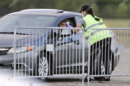 Worker takes the temperature of a person arriving at Darlington Raceway before the Real Heroes 400 NASCAR Cup Series auto race, in Darlington, S.C. NASCAR, which has been idle since March 8 because of the coronavirus pandemic, makes its return at the track Sunday