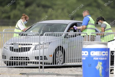 Workers take the temperatures of people arriving at Darlington Raceway before the Real Heroes 400 NASCAR Cup Series auto race, in Darlington, S.C. NASCAR, which has been idle since March 8 because of the coronavirus pandemic, makes its return at the track Sunday