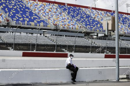 An official sits on a wall in front of empty seats in Darlington Raceway before the Real Heroes 400 NASCAR Cup Series auto race, in Darlington, S.C. NASCAR, which has been idle for 10 weeks because of the coronavirus pandemic, makes its return at the track Sunday