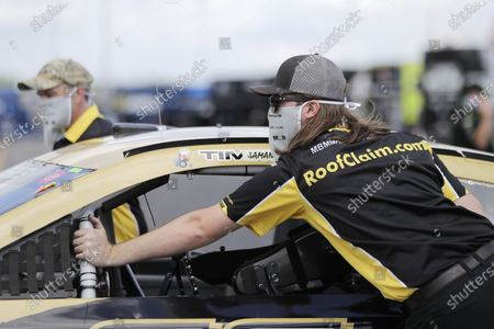 Crew members wear masks as they push the car of Timmy Hill through the infield before the Real Heroes 400 NASCAR Cup Series auto race, in Darlington, S.C. NASCAR, which has been idle for 10 weeks because of the coronavirus pandemic, makes its return at the track Sunday