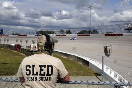 Member of a security team watches during the NASCAR Cup Series auto race, in Darlington, S.C