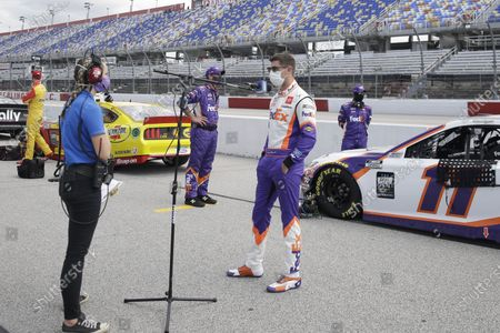 Driver Denny Hamlin (11) is interviewed before the NASCAR Cup Series auto race, in Darlington, S.C
