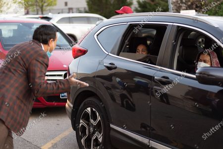 Stock Photo of The Islamic Society of North America (ISNA) hosts a drive-thru iftar in the holy month of Ramadan. MPP for Mississauga-Malton, Deepak Anand, volunteers to hand out meals to iftar attendees as they drive up.