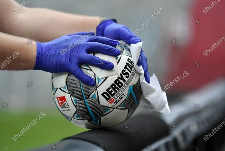 Ball boy with rubber gloves disinfects the Derbystar league ball
