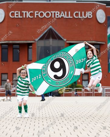 Stock Photo of Young Celtic fans Evie Thompson (7) and Layla Hastie (9) celebrate outside Celtic Park in Glasgow, Britain, 18 May 2020, after the club was confirmed Scottish league champions, their 9th win in a row. The Scottish Professional Football League (SPFL) announced that Celtic was proclaimed champion after the Scottish Premiership 2019-2020 season has been declared over with immediate effect due to the ongoing coronavirus COVID-19 pandemic.