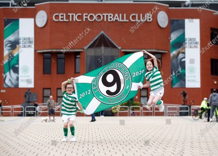 Stock Image of Young Celtic fans Evie Thompson (7) and Layla Hastie (9) celebrate outside Celtic Park in Glasgow, Britain, 18 May 2020, after the club was confirmed Scottish league champions, their 9th win in a row. The Scottish Professional Football League (SPFL) announced that Celtic was proclaimed champion after the Scottish Premiership 2019-2020 season has been declared over with immediate effect due to the ongoing coronavirus COVID-19 pandemic.