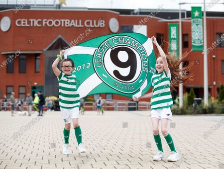 Stock Picture of Young Celtic fans Evie Thompson (7) and Layla Hastie (9) celebrate outside Celtic Park in Glasgow, Britain, 18 May 2020, after the club was confirmed Scottish league champions, their 9th win in a row. The Scottish Professional Football League (SPFL) announced that Celtic was proclaimed champion after the Scottish Premiership 2019-2020 season has been declared over with immediate effect due to the ongoing coronavirus COVID-19 pandemic.