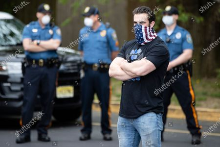 Atilis Gym co-owner Ian Smith stands outside the gym in Bellmawr, N.J., as police look on. The gym in New Jersey reopened for business early Monday, defying a state order that shut down nonessential businesses to help stem the spread of the coronavirus