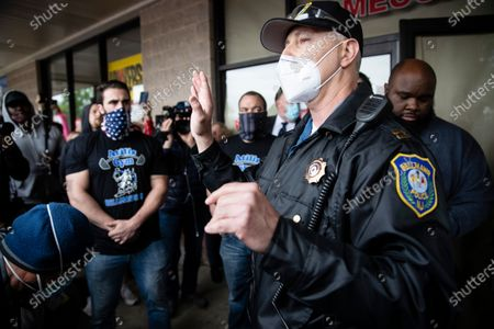 Police officer addresses supporters of Atilis Gym co-owners Frank Trumbetti, center, Ian Smith, left, outside their gym in Bellmawr, N.J., . The gym in New Jersey reopened for business early Monday, defying a state order that shut down nonessential businesses to help stem the spread of the coronavirus