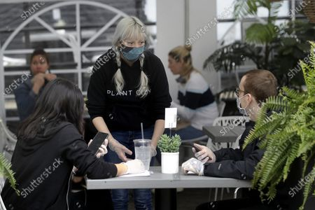Stock Image of Server Katie Maloney, of Providence, R.I., center, wears a mask out of concern for the coronavirus while assisting patrons in an outdoor seating area at Plant City restaurant, in Providence, . Rhode Island allowed restaurants to provide service with outdoor seated dinning Monday for the first time since the beginning of the government imposed lockdown due to the coronavirus pandemic