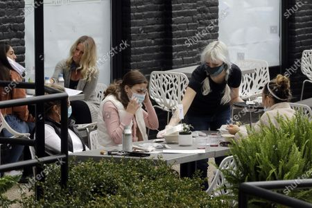 Server Katie Maloney, of Providence, R.I., top right, wears a mask out of concern for the coronavirus while assisting patrons in an outdoor seating area at Plant City restaurant, in Providence, . Rhode Island allowed restaurants to provide service with outdoor seated dinning Monday for the first time since the beginning of the government imposed lockdown due to the coronavirus pandemic