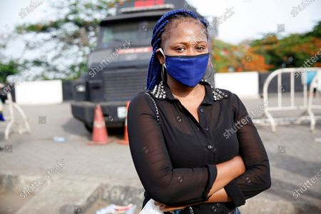 A woman wearing a blue face mask and a tinted hair style stands in front of a police armored vehicle at a bus stop in Lagos, Nigeria, 18 May 2020. With a population of about 21 million people, the Lagos metropolitan government is considering a full reopening of the critical sectors of its economy including religious houses, after two weeks of partial ease of lockdown to curb the spread of coronavirus disease.